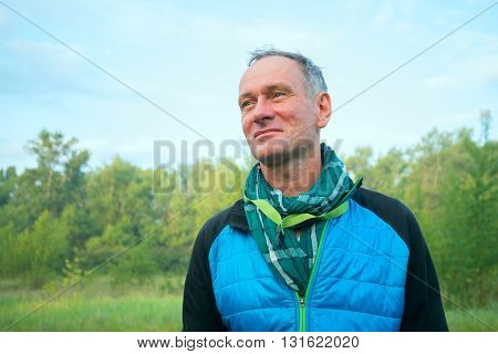 Portrait of a tired smiling traveler standing on the old road on the background of the green trees early in the morning after a sleepless night in the journey. Blurred background.