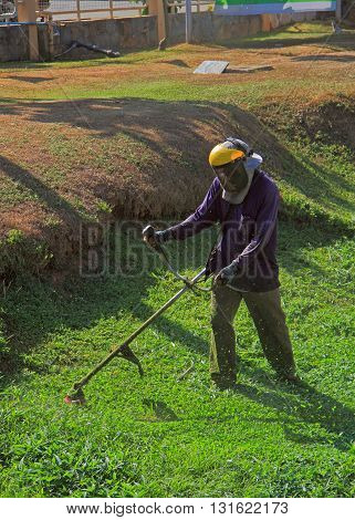 Krabi Thailand - March 29 2015: man is trimming grass outdoor in Krabi province of Thailand