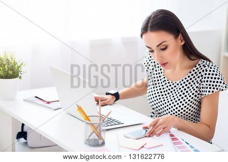 What is the news.   Nice pleasant concentrated woman sitting at the table and using cell phone while working in the