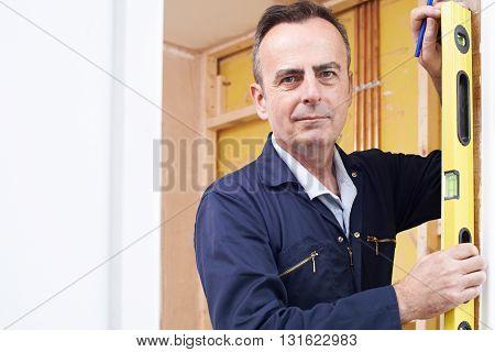 Portrait Of Builder Checking Work With Spirit Level
