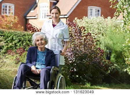 Portrait Of Carer Pushing Senior Woman In Wheelchair