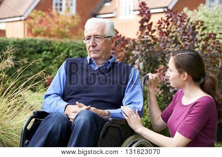 Adult Daughter Comforting Senior Father In Wheelchair