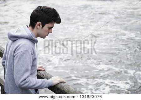 Depressed Young Man Contemplating Suicide On Bridge Over River