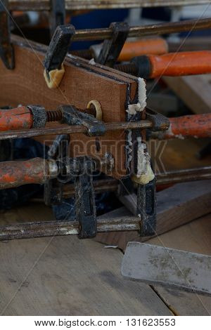 Clamps holding two piece of wood together on a workbench at a boatyard
