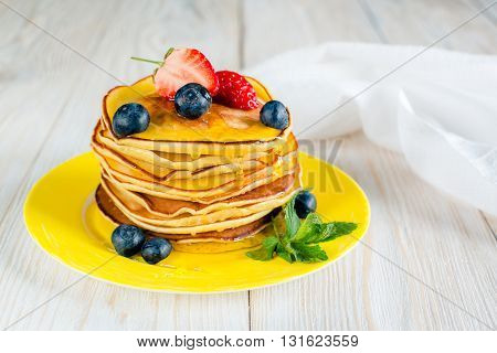 Pancakes on a yellow plate with honey and berries on a white background.