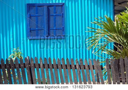 Blue window shutters on wall of a container home