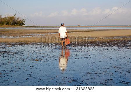 Mauritian fisherman walking in the shallow lagoon at sunrise