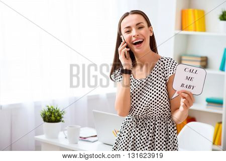 Call me.  Pleasant cheerful smiling beautiful woman talking on cell phone and expressing gladness while standing in the office
