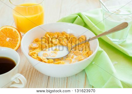 boul with corn flakes and spoon in it and green napking on a table