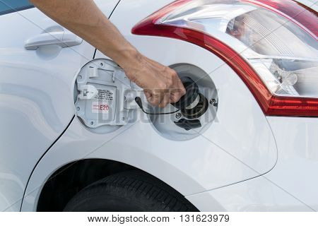 Hand opening the oil filler cap. cap, car, gas, service, hand, oil,