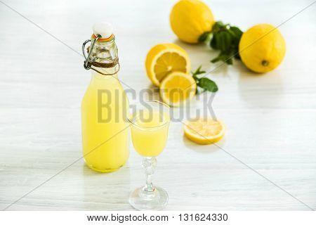 The italian traditional liqueur limoncello with lemon