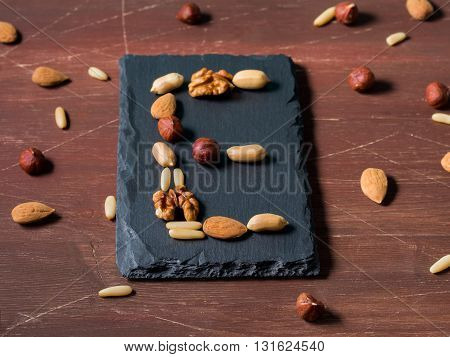 Vitamin E concept with different nuts - almonds, hazelnuts, walnuts, pine nuts on dark wooden background. angle view