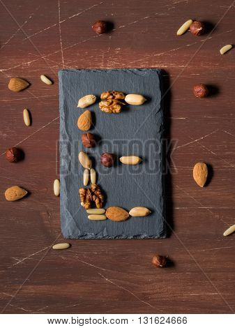 Vitamin E concept with different nuts - almonds, hazelnuts, walnuts, pine nuts on dark wooden background. top view, vertical image