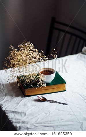 Fresh hot coffee on a pile of books on a table covered with a white cloth at the window. Still life. Rustic dark stying.