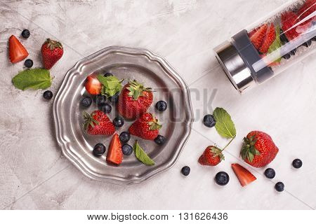 Infused berry water with mint leaves and ingredients over stone background. Top view. Space for text