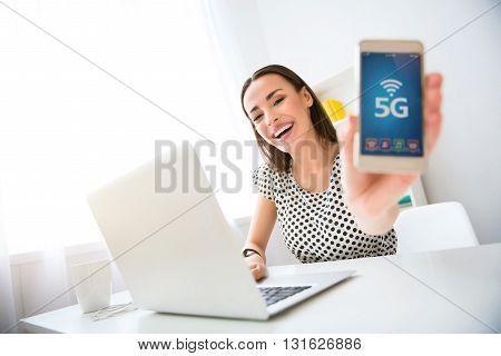 New innovation. Cheerful delighted beautiful smiling woman sitting at the table and holding cell phone while expressing gladness