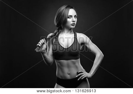 Sexy young woman standing on grey background. Fitness female looking at camera. Concept of sport and healthy lifestyle.