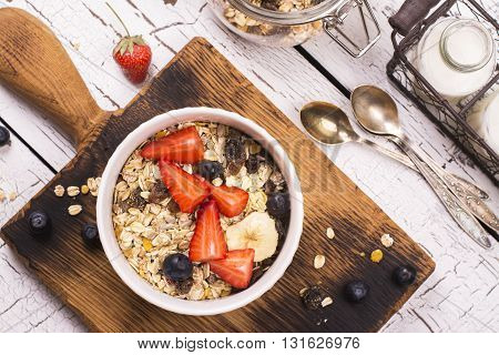 Homemade granola with fruits, berries and milk over wooden background. Rustic style. Top view. Space for text