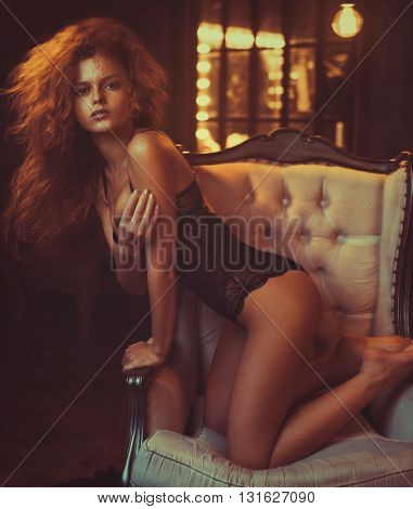 Young woman with red hair indoors portrait on chair. Vintage film style soft warm colors.