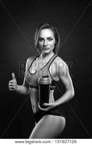Beautiful sexy fitness girl with shaker on a dark background