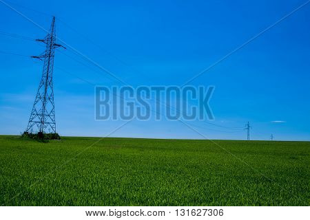 Electric pylons on a green field and blue sky