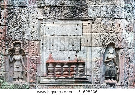Detail of a carved stone wall in Angkor temples complex Siem Reap Cambodia