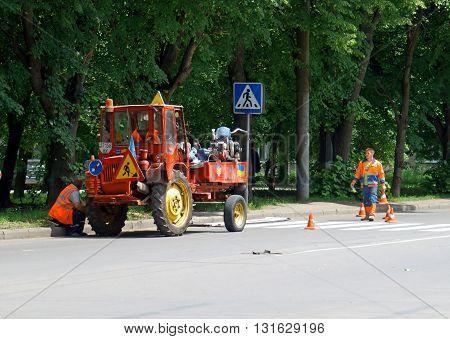 Khmelnitsky Ukraine 26 may 2016: Workers restoring a road marking on the street Khmelnitsky.