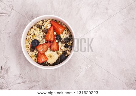 Homemade granola with fruits, berries and milk over stone background. Top view. Space for text