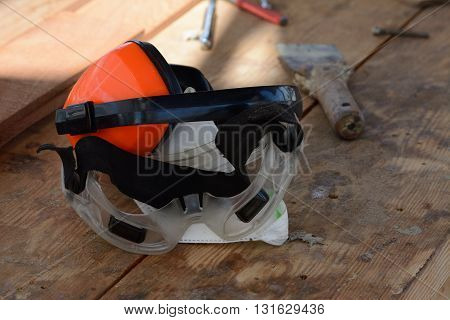 Earmuffs and googles on a workbench in the shades