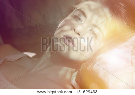 young lady lying on the bed in the morning sun