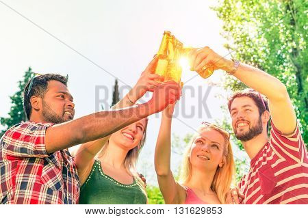 Multiracial group cheering friends party hands up with beers outdoors - Teenagers happy couples drinking and fun moments in summer vacation - Concept of happiness youth and teamwork