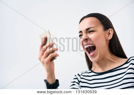 On the edge of fury.  Emotional bad tempered  cheerless woman holding cell phone and screaming while standing isolated on white background