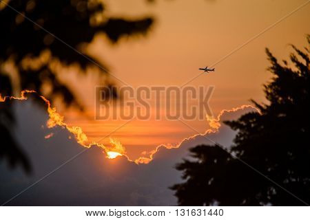 An airplane flies through during the sunset