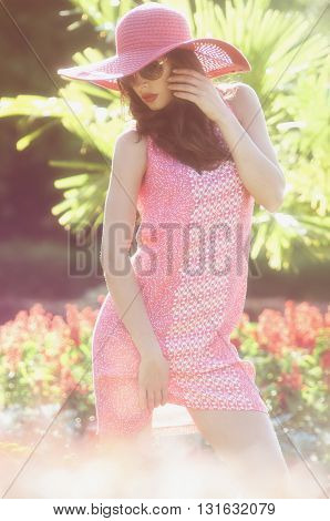 girl in a pink dress and sunglasses in the garden