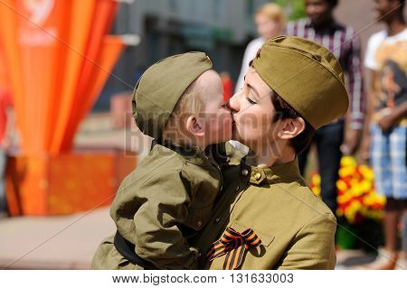 Orel Russia - May 9 2016: Celebration of 71th anniversary of the Victory Day (WWII). Mama kissing her baby in military uniform with red flags background