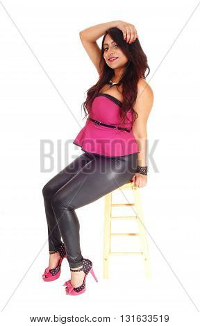A beautiful young East Indian woman sitting on a chair in black tights and blouse one hand on head isolated for white background.