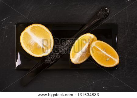 Cut lemons over black scratched stone background. Top view. Selective focus