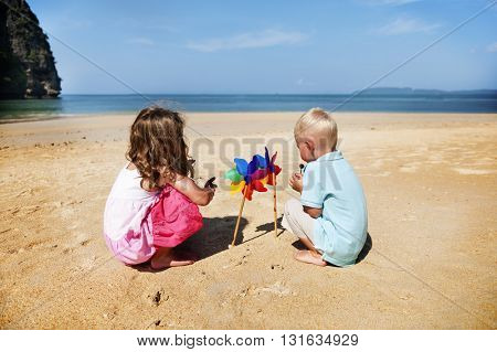 Children Playing Pinwheel Beach Summer Holiday Concept