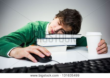 Young student in green pullover sleeping on desk with book coffee cup computer keyboard and mouse