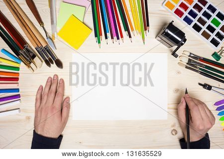 Top view of artist's hands with pencil on wooden desktop with blank paper and drawing tools. Mock up
