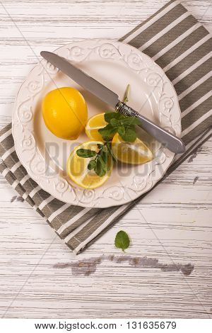 Cut lemons and mint sprigs over white wooden table. Ingredients for lemonade