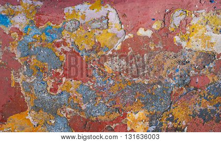 Peeling paint on wall grunge texture. Pattern of rustic red and yellow grunge material closeup.