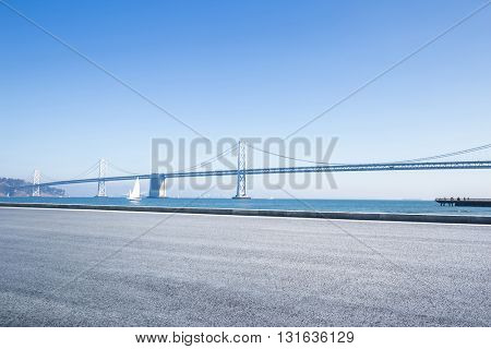 empty asphalt road near sea with gold gate bridge in blue sky