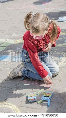 Rostov-on-Don Russia- May 22, 2016: Girl in fancy dress draws on the sidewalk at the festival