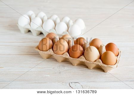 brown and white eggs on a white wooden table
