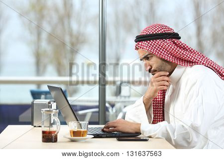 Side view of an arab saudi man worried working with a laptop in a coffee shop interior with the terrace in the background