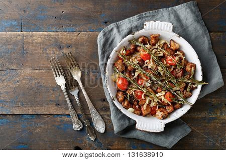 Roasted Chicken Meat with rosemary tomato and onion on frying pan on rustic wooden background. Top view