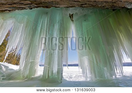 Ice curtains at Lake Superior's Grand Island in Munising Michigan. Pictured Rocks National Lakeshore can be seen in the background of this winter scene.