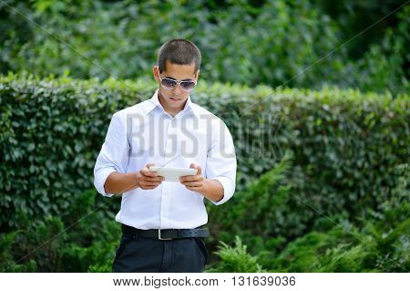 Young Man In Sunglasses Using His Tablet In The Green Nature