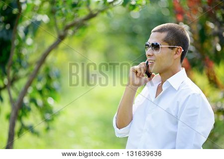 Young Smiling Man Talking On A Mobile Phone